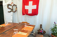 Switzerland. Canton Ticino. The family Cereghetti runs the Agriturismo Dosso dell'Ora on Monte Generoso. They celebrated a few days before the fiftieth anniversary of Marina Cereghetti. The wooden table is set for the lunch service. The flag of Switzerland displays a white cross in the centre of a square red field. The white cross is known as the Swiss cross. A plaster statue of the Virgin Mary stands on the ground in a floral decoration. 4.07.2020 © 2020 Didier Ruef