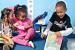 Education Preschool 3-4 year olds two girls and a boy laughing and enjoying each other's company playing with picture books.