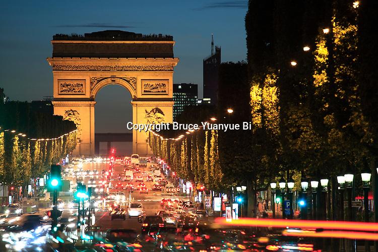 The night view of Avenue des Champs-Élysées with Arc de Triomphe in the background. Paris. France