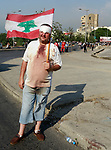 A protester holds the flag of Lebanon on the first anniversary of the blast that ravaged the port and the city, in Lebanon's capital Beirut, on August 2021. Hundreds of Lebanese marched on August 4 to mark a year since a cataclysmic explosion ravaged Beirut, protesting impunity over the country's worst peacetime disaster at a time when its economy was already in tatters. Photo by Marwan Bou Haidar