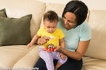 10 month old baby girl at home with mother shown bell toy, mother demonstrating how it works