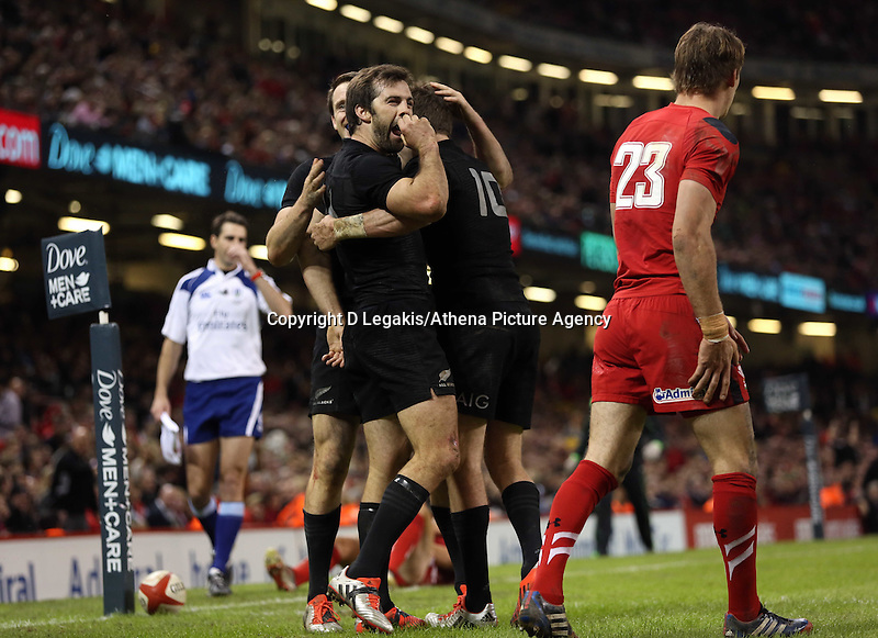 Pictured: Beauden Barrett of New Zealand is mobbed by team mates celebrating his try who mock Liam Williams of Wales (R) Saturday 22 November 2014<br /> Re: Dove Men Series 2014 rugby, Wales v New Zealand at the Millennium Stadium, Cardiff, south Wales, UK.