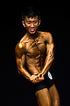 Fong Chi Him flexes muscles for judges on stage during the Hong Kong Bodybuilding Championship on 29 June 2014 at the Queen Elizabeth Stadium Arena in Hong Kong, China. Photo by Aitor Alcalde /  Power Sport Images