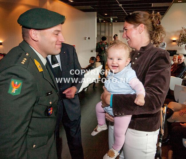 Ugchelen 160910 kaptein meijs hangt zijn 6 maand oude dochter Frederique de kindermedaille Uruzgan om, nadat hij zelf zijn medaille had gekregen.<br /> Rechts zijn vrouw Carine.<br /> Foto Frans Ypma APA-foto
