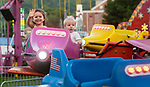 THOMASTON, CT 072821JS20 Elyse Brady, 2, of Thomaston waves to her mother while she and 18-month-old Liam Sayers, enjoy their time on one of the kids rides during opening night of the annual Thomaston Fire Department's carnival Wednesday at Sanford Field. The carnival continues through Saturday with fireworks on Friday night at 9 pm and a parade Saturday at 6pm. <br /> Jim Shannon Republican American