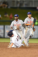 St. Lucie Mets second baseman Dilson Herrera (13) turns a double play as shortstop Phillip Evans (28) backs up the play with outfielder Travis Harrison (17) sliding in during a game against the Fort Myers Miracle on April 18, 2014 at Hammond Stadium in Fort Myers, Florida.  St. Lucie defeated Fort Myers 15-9.  (Mike Janes/Four Seam Images)