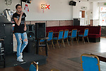 Leysdown on Sea, Isle of Sheppey, Kent, UK 2014. Young woman singing in empty working class pub.