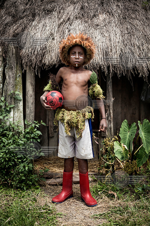 Abinus Kuban, 10, holds a ball which he and his friends play with. The children from his village, Arigaram, wear secondhand clothes on a day-to-day basis but wear 'kotekas' (gourd penis sheaths) for cultural festivals and folk dances.