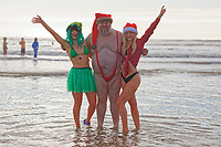 Pictured: A man in a mankini and a Santa hat poses with two young women in the sea. Wednesday 25 December 2019<br /> Re: Hundreds of people in fancy dress, have taken part in this year's Porthcawl Christmas Swim in south Wales, UK.