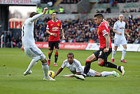 SWANSEA, WALES - FEBRUARY 21: Gylfi Sigurdsson of Swansea (L) takes a shot against Marcos Rojo of Manchester (R), Wayne Routledge of Swansea on the ground (C) during the Barclays Premier League match between Swansea City and Manchester United at Liberty Stadium on February 21, 2015 in Swansea, Wales.