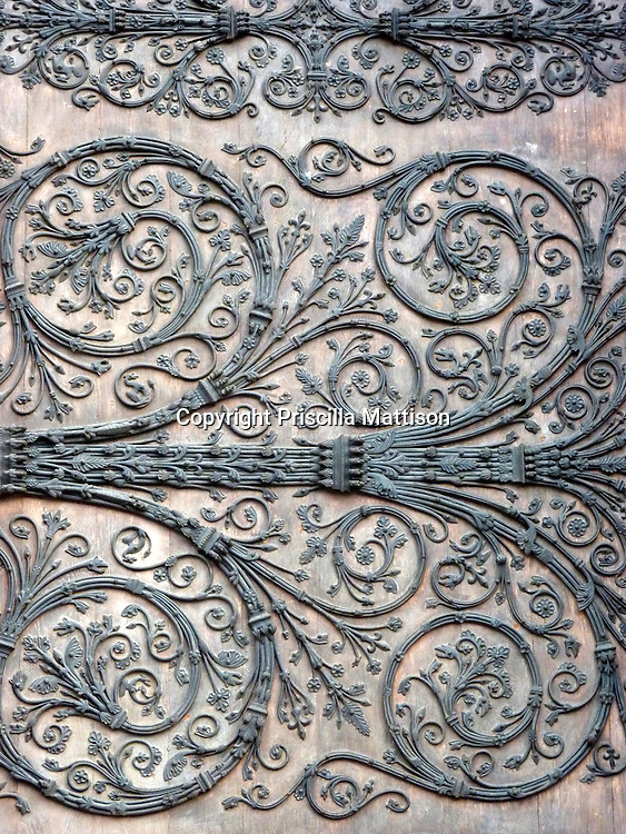 Paris, France - February 2, 2011:  A wooden doorway at Notre Dame Cathedral is covered with delicate decoration.