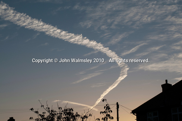 Altocumulus clouds at daybreak with a jet's contrail.