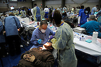 Mike Petty is seen by Dr Boyd in the Remote Area Medical (RAM) dental area that handles 30 patients at a time. All dentists and dental assistants are volunteers. Over the weekend at Soft Shell, Knott County, in the Appalachian mountains of eastern Kentucky, the congressional district with the nation's lowest life expectancy, RAM volunteers saw 822 needy people. 95 percent of people seen were provided with dental or optical care. RAM was founded in 1985 to provide free health, dental and eye care in the developing world. However, RAM now provides 60 percent of its services in the US, providing for the estimated 47 million Americans without health insurance..