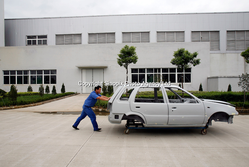 A worker fushes the frame of a car at the Geely Automobiles Factory in Taizhou, Zhejiang Province, China. Along with other auto makers in China, Geely is now looking overseas to sell its vehicles as stock increases and domestic margine declines. China is currently the world's 4th largest auto maker, plans to boost vehicle and automobile components exports by 15 folds to more than 120 billion yuan (15 billion US) in the next 10 years.