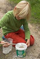 Kinder gießen Tierspur aus Gips, Junge rührt Gips in altem Becher an