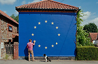 Remain voter Ben Gollion finishing a mural of the EU flag on his house watched Norfolk,UK.