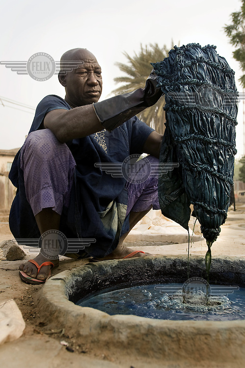 A man dyes fabric with blue indigo in one of Kano's ancient dye pits. These have been operating for at least 500 years but the industry has declined in recent times as cheap, chemically dyed, imported cloth has underminded the local fabric industry.