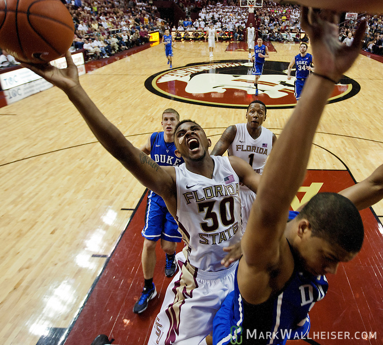 FSU's Ian Miller (30) drives to the basket over the back of Duke's Andre Dawkins (20) when the 15th ranked Florida State Seminoles fell 74-66 to the 4th ranked Duke Blue Devils in an NCAA basketball game in Tallahassee, Florida November 23, 2010.