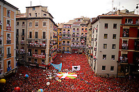 Participants celebrate during the 'Chupinazo' to mark the start at noon sharp of the San Fermin Festival on July 6, 2012 in front of the Town Hall of Pamplona, northern Spain. The festival is a symbol of Spanish culture, despite heavy condemnation from animal rights groups, and attracts thousands of tourists to watch the bull runs. (c)Pedro ARMESTRE