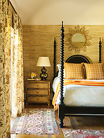 Textures abound in the guest room, such as the chunky raffia on the walls and the bamboo chest of drawers. The room is decorated in soft neutrals with pops of sunset tangerines and peaches, set off by dashes of white. The wood floor is scraped oak.