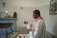 """Switzerland. Canton Ticino. Grancia. Reverend Father Gerald Chukwudi Ani celebrates the Sunday mass at home and transmits it live on YouTube. Don Gerald Chukwudi Ani, originally from Nigeria, is a catholic priest from the Diocese of Lugano. Sacramental bread (Latin: hostia, Italian: ostia), sometimes called altar bread, Communion bread, the Lamb or simply the host, is the bread or wafer used in the Christian ritual of the Eucharist. Eastern and Western traditions both require that it be made from wheat. Transubstantiation is, according to the teachings of the Roman Catholic Church, the change of substance or essence by which the bread and wine offered in the sacrifice of the sacrament of the Eucharist during the Mass, become, in reality, the body and blood of Jesus Christ. Due to the spread of the coronavirus , the Federal Council has categorised the situation in the country as """"extraordinary"""". It has issued a recommendation to all citizens to stay at home, especially the sick and the elderly. From March 16 the government ramped up its response to the widening pandemic, ordering the closure of bars, restaurants, sports facilities and cultural spaces. Celebrating masses is prohibit in order to avoid people meeting together. On the wall, a wooden crucifix with Jesus Christ on the cross. On the shelf (Left to right) : A swiss clock. A picture taken at a baptism ceremony in Italy. A statue of Our Lady of Fátima (Our Lady of the Holy Rosary of Fátima). A wooden model of a catholic church. A traditional Igbo mask (Igbo is an ethnic tribe of southeastern Nigeria). On the wall (R) a painting about the Holy Trinity. The Christian doctrine of the Trinity holds that God is three consubstantial persons or hypostases—the Father, the Son (Jesus Christ), and the Holy Spirit—as """"one God in three Divine Persons"""". The three Persons are distinct, yet are one """"substance, essence or nature"""". YouTube is an American online video-sharing platform. Grancia is a municipality in the"""