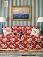 A corner of the dayroom concentrates the eye on Cameron's confident detailing. A comfortable sofa is accented with a bold red floral pattern that is reversed for the cushions, the rug, small cushion, standard lamps and striped wallpaper continue the quirky nautical theme.