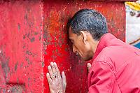 Nepal, Kathmandu.  Man Worshiping at Hanuman Statue, Durbar Square.