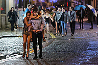 Pictured: A young woman gets a piggy back ride by a young man. Sunday 31 December 2017 and 01 January 2018<br /> Re: New Year revellers in Wind Street, Swansea, Wales, UK
