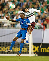 CHARLOTTE, NC - JUNE 23: Stephane Abaul #20 and Edson Alvarez #4 contest a header during a game between Mexico and Martinique at Bank of America Stadium on June 23, 2019 in Charlotte, North Carolina.