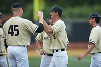 Wake Forest Demon Deacons relief pitcher Carter Bach (18) is congratulated by teammates after getting the third out in the 7th inning against the Miami Hurricanes at David F. Couch Ballpark on May 11, 2019 in  Winston-Salem, North Carolina. The Hurricanes defeated the Demon Deacons 8-4. (Brian Westerholt/Four Seam Images)