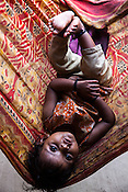 11 month Sita Mandal lies on the hammock in her house in Bhardaha in Saptari, Nepal.