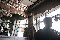 Wednesday 15 July, 2015: A Houthi fighter attends a barbershop damaged by a bomb blast on the day before Eid in one downtown street of Sa'dah, a city subdued to heavy bombarments carried out by the Saudi-led coalition in the northern province of Sa'dah, the stronghold of the Houthi's movement in Yemen. (Photo/Narciso Contreras)