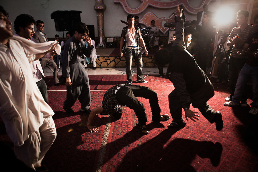 Hundreds of family members and friends - carefully divided between side's for men and women - attend a wedding at the lavish Mumtaz Majal wedding hall in Kabul. Glistening wedding halls dot the Kabul city scape and their attendance - which always includes large dinners and energetic dancing - is a mainstay of Kabuli social life. Summer 2010.
