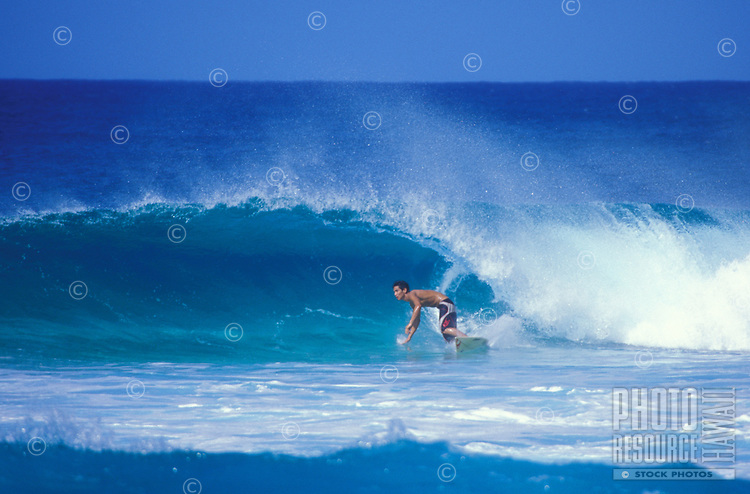 Surfer on a wave in clear blue water at Ehukai Beach, North Shore of Oahu