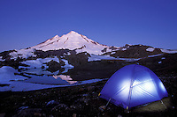 Backpacking tent glowing below night sky, near Yellow Aster Butte, North Cascades, Whatcom County, Washington, USA