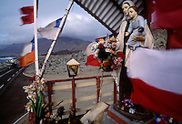 Flags and statuary decorate an alter that marks the Pan American highway in a desolate section of northern Chile.