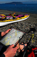 Male paddler consults nautical chart in preparing for a day of paddling in the San Juan Islands, Sea Kayaking the San Juan Islands, WA.