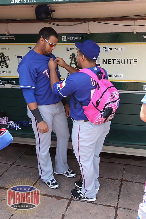 OAKLAND, CA - MAY 15:  Joseph Ortiz #58 of the Texas Rangers talks with teammate Nelson Cruz #17 in the dugout while wearing a pink backpack before the game against the Oakland Athletics at O.co Coliseum on Wednesday May 15, 2013 in Oakland, California. Photo by Brad Mangin