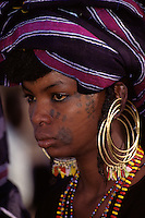 Akadaney, Niger, Africa - Fulani Wodaabe Woman at Geerewol, watching Male Dancers in the Male Beauty Contest.  Note facial tattoos and scarification.