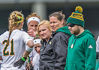 25 April 2015: University of Vermont Catamount Head Coach Jen Johnson stands with her assistants as she glances down the sidelines during game action against the University of New Hampshire Wildcats at Virtue Field in Burlington, Vermont. The Lady Catamounts defeated the Lady Wildcats 12-10 in the final game of the season, advancing to the America East playoffs. Mandatory Credit: Ed Wolfstein Photo *** RAW (NEF) Image File Available ***