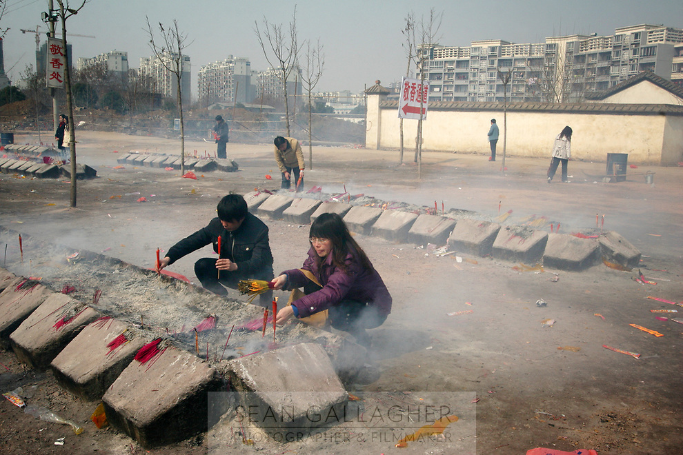 CHINA. Hubei Province. Wuhan. People burning incense in a temple Wuhan (population 4.3 million) is a sprawling city that sits on both sides of the Yangtze River.  2008