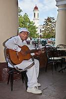 Cuba, Cienfuegos.  Afro-Cuban Guitar Player outside a Cafe.  Church of La Purisima Concepcion in Background.