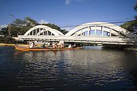 Outrigger canoe paddling under the Anahulu Bridge, Haleiwa, North Shore of Oahu