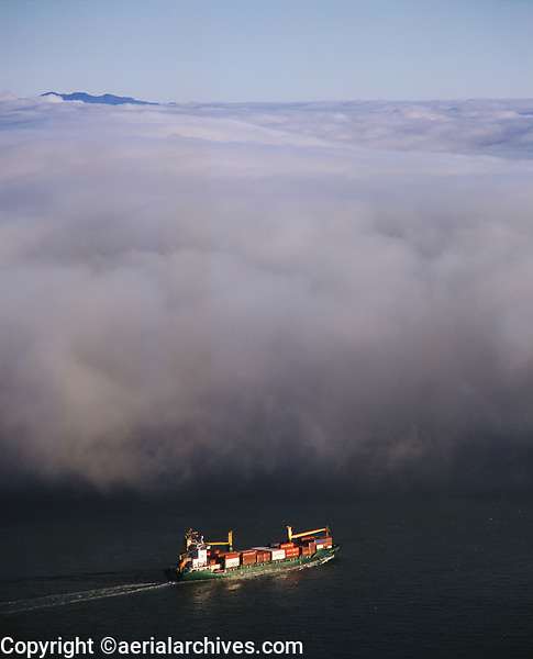 aerial photograph of a loaded containership about to pass under the fog in San Francisco bay, California