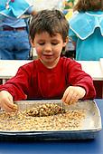 MR/Schenectady, New York.Yates Arts-in-Education Magnet school/ Pre-Kindergarten.Boy (4) does bird feeder project (peanut butter is spread on pine cone and rolled in bird seed)..MR:Gab1.PN#:26242     FC#:20928-00116.scan from slide.© Ellen B. Senisi