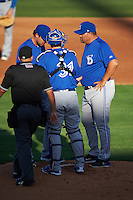 Dunedin Blue Jays pitching coach Jim Czajkowski (right) talks with starting pitcher Tom Robson (left) and catcher Danny Jansen (31) as umpire J.C. Velez comes to break up the meeting during a game against the Clearwater Threshers on April 8, 2016 at Bright House Field in Clearwater, Florida.  Dunedin defeated Clearwater 8-3.  (Mike Janes/Four Seam Images)