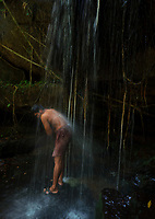 "Local Khmer man washing and cleaning himself under the waterfall at Kbal Spean (""Bridge Head"") is an Angkorian era archaeological site on the southwest slopes of the Kulen Hills to the northeast of Angkor in Siem Reap District, Siem Reap Province, Cambodia. It is situated along a 150m stretch of the Stung Kbal Spean River, 25 kilometres (16 mi) from the main Angkor group of monuments, which lie downstream.<br />