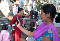 Kathmandu, Nepal.  Young Nepali Woman Takes a Photo of a Friend on the Stairs Leading to Swayambhunath Temple.  Note the nose ring and the two ear rings.