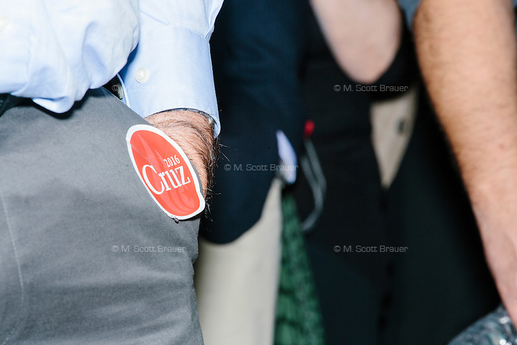 """A man has a Cruz campaign sticker on his pants while he listens to Texas senator and Republican presidential candidate Ted Cruz speak to attendees at an event called """"Smoke a cigar with Ted Cruz"""" at a house party at the home of Linda & Steven Goddu Salem, New Hampshire."""