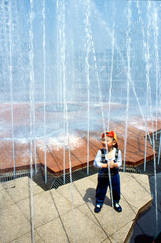 China. Shanghai. Downtown. City center. Renmin Square near the People square. Young boy dressed on a Sunday best plays in the middle of jets of water. © 2002 Didier Ruef